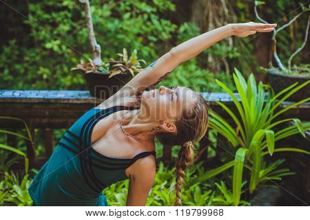 Pretty Young Woman Doing Yoga Outside In Natural Environment