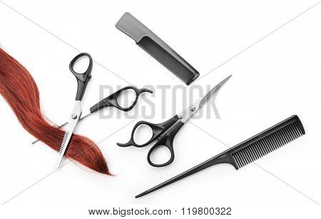 Hairdresser's scissors with combs, strand of red hair, isolated on white