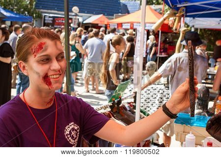 Woman Uses Mirror To Check Out Zombie Makeup At Event