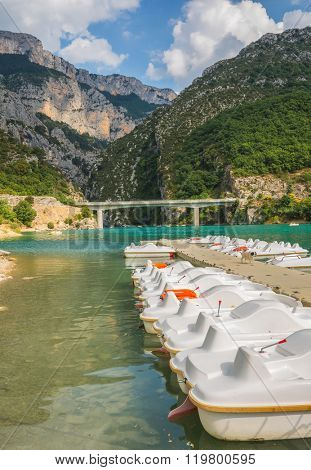 Big bridge across the canyon and river Verdon. Wooden pier with white catamaran.  National park Merkantur, Provence, France