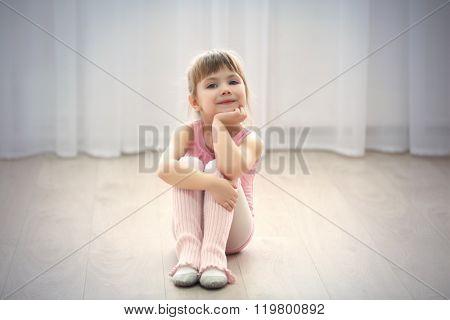 Little cute girl in pink leotard sitting on floor at dance studio