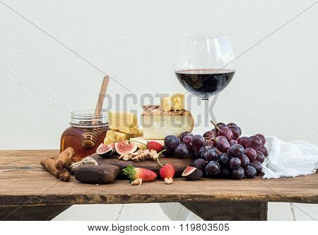 Glass of red wine, cheese board, grapes,fig, strawberries, honey and bread sticks  on rustic wooden