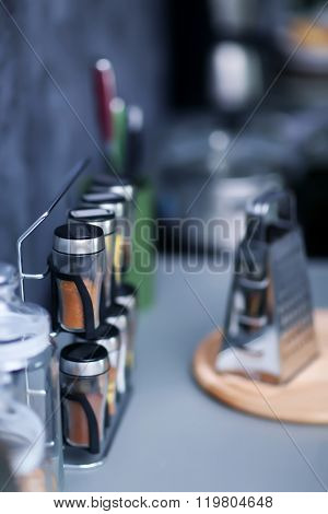 Spices with metal grater on modern kitchen table, close up
