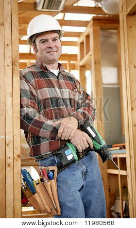 A handsome construction worker on the job-site with his tools, ready to work.  Authentic and accurate content depiction.
