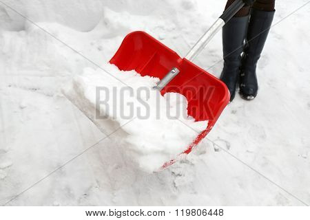 Woman removing snow with snow shovel