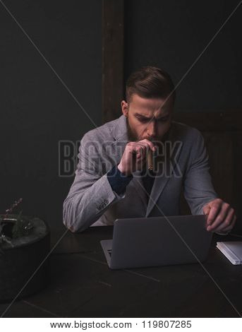 Attractive bearded man is working with a laptop