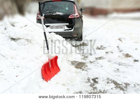 Winter concept. Red shovel for cleaning the driveway of snow