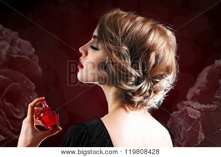 Beautiful young woman with perfume bottle on dark flower background