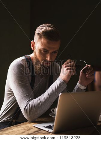 Cheerful bearded guy is working with a laptop