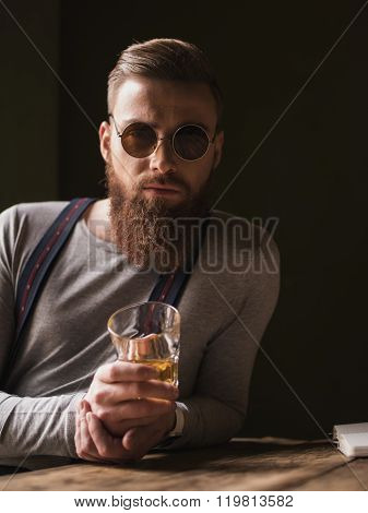 Handsome young hipster is enjoying alcohol drink