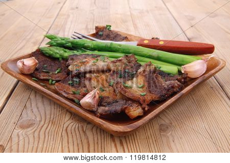dinner of hot beef pork meat grilled ribs with asparagus and garlic over wooden background table