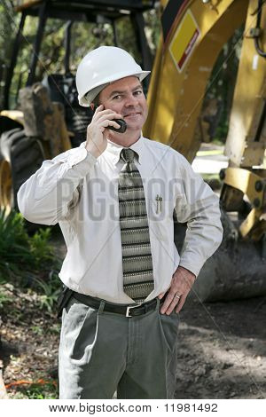 A proud, confident engineer on the construction site, talking on the telephone.