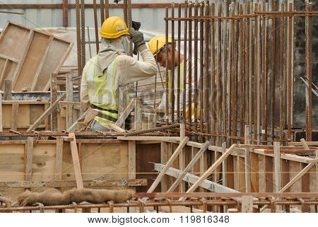 Two construction workers fabricating ground beam steel reinforcement bar