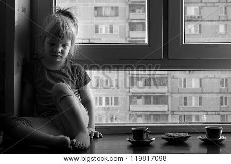 Sad child sits on a window sill of the window