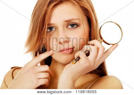 Thinking teenage woman holding magnifying glass