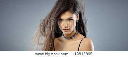Portrait of wild, sexy woman with long hair, looking at camera.
