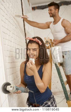 Smiling young woman renovating home, using grinding machine, boyfriend behind.
