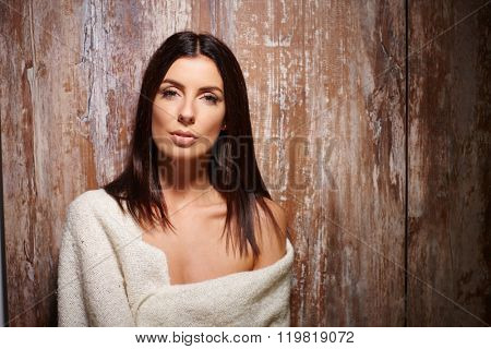 Portrait of attractive young woman in blanket front of antique wooden wall.