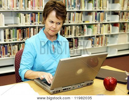 A school librarian frowns as she reviews students on-line activity.