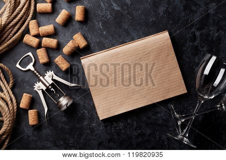 Wine corks, corkscrew and notepad over dark stone background. Top view with copy space