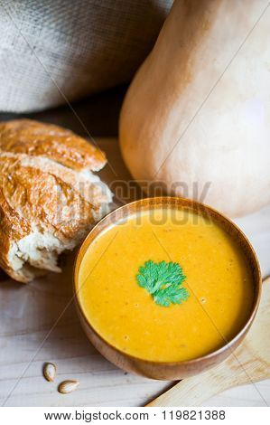 Butternut Squash Soup With Homemade Bread On Wooden Background