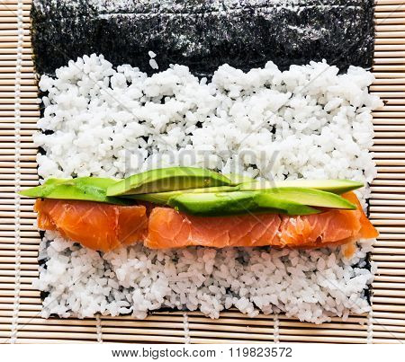 Preparing sushi background. Salmon, avocado, rice on seaweed. View from the top.
