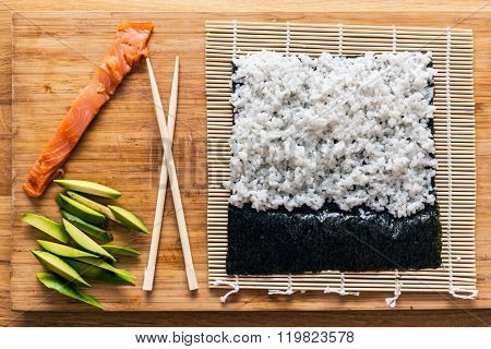 Preparing sushi. Salmon, avocado, rice on seaweed and chopsticks on wooden table. View from the top.