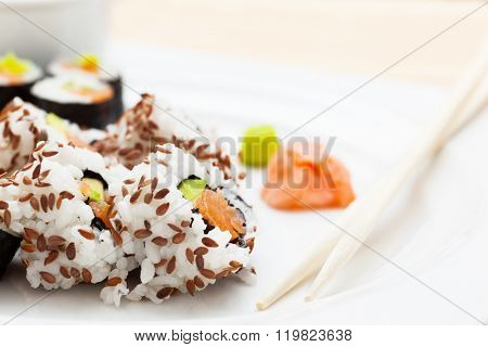 Sushi with salmon, avocado, rice in seaweed and chopsticks served on a plate with wasabi and ginger. Japanese, Asian healthy food.