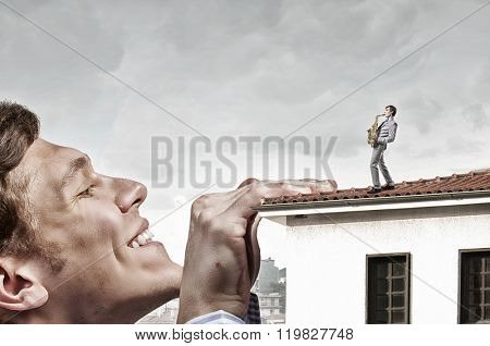 Giant man looking on saxophonist playing