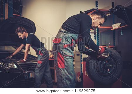 Professional car  mechanic balancing car wheel on balancer in auto repair service.