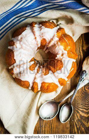 Bundt Cake With White Glaze On Rustic Background