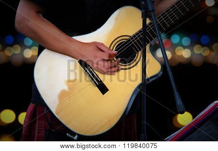 Guitarist Playing Acoustic Guitar With Blur Lights Background