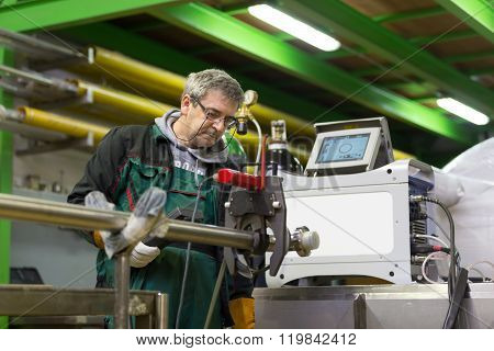 Industrial worker setting orbital welding machine.