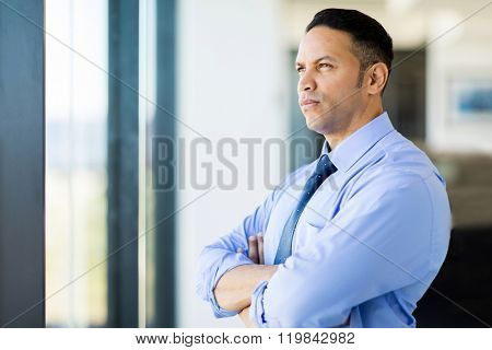 thoughtful mid age businessman with arms crossed