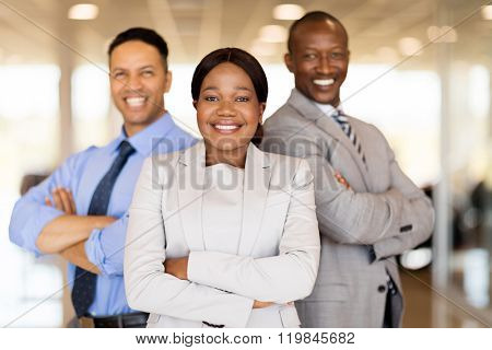 multiracial vehicle sales team with arms crossed inside car showroom