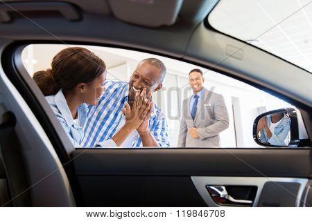 excited african couple at the dealership buying new car
