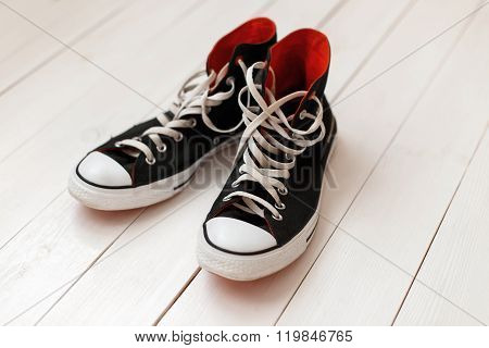 Old Black Sneakers With Red On Wooden Background