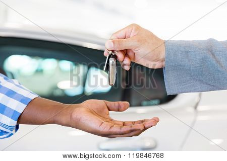close up of car dealer handing over new car key to customer at showroom