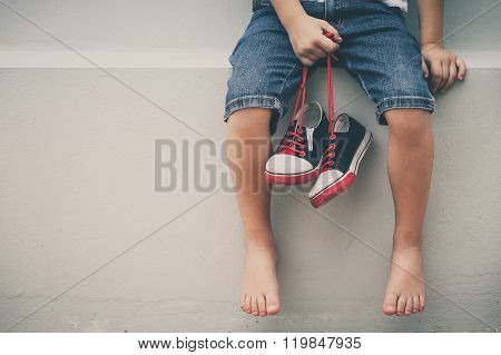 Little Boy  Sitting Near The House And Keeping The Youth Sneakers In His Hands Of.