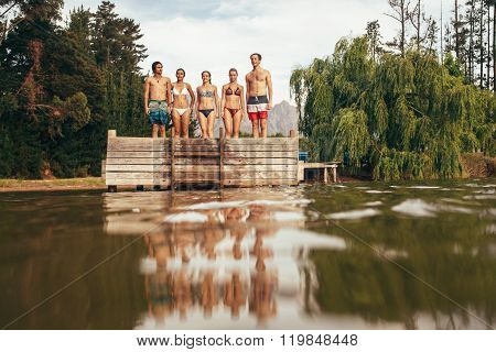 Young Friends Standing On Jetty At The Lake
