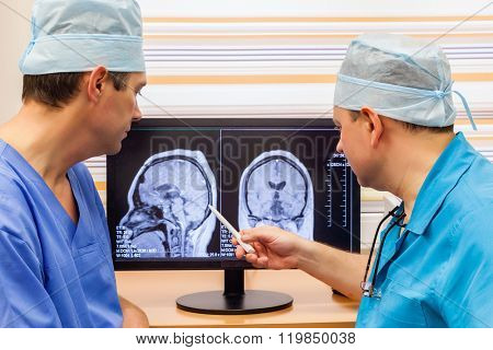 Two doctors examining an MRI scan of the Brain on Monitior