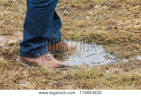 Feet Of A Person Standing In A Puddle Of Water