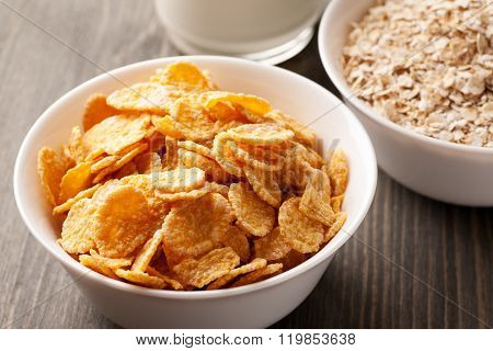 Cornflakes And Oatmeal In White Bowls With Milk