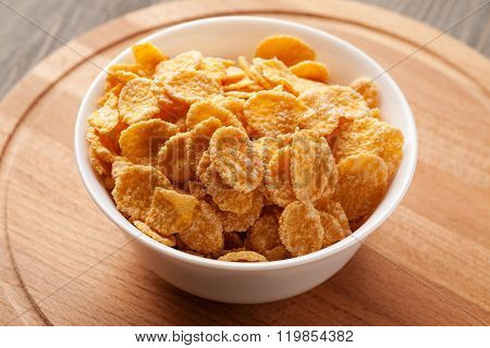 Yellow Cornflakes In White Bowl On Wooden Board
