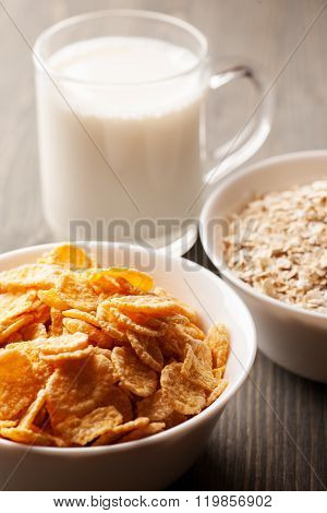 Cornflakes And Oatmeal In White Bowls With Glass Of Milk