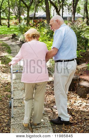 Senior couple out for a walk.  The husband is helping his wife with her walker.