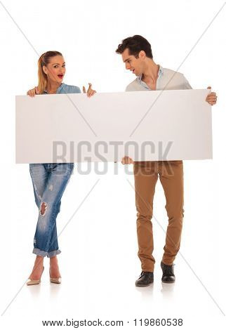 handsome couple posing in isolated studio background holding a blank white sign. man is looking away while woman is looking at the camera with legs crossed