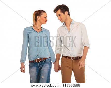 cute couple walking in white isolated studio background, holding hands and looking at each other