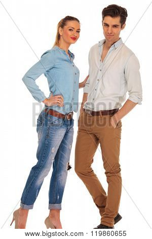 attractive boyfriend and girlfriend posing in white isolated studio background while looking at the camera. the man has both hands in pockets and woman is touching his arm