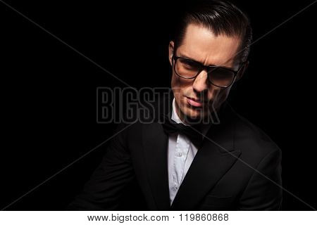 dark portrait of attractive businessman wearing glasses posing in studio background looking at the camera